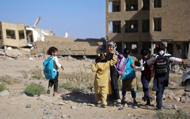 Des fillettes yéménites devant une école détruite par une frappe aérienne dans la ville de Taëz, dans le sud du Yémen, le 16 mars 2017. (Crédit : Ahmad Al-Basha/AFP)
