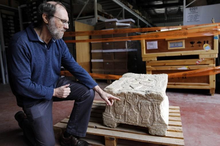 Le professeur Gideon Avni, qui dirige la division archéologique de l'Autorité israélienne des Antiquités, présente la pierre originale de Magdala, qui porte la ménorah à sept branches découverte dans une synagogue de Galilée et date de l'époque du deuxième Temple (entre 50 avant l'ère commune et 100 après), dans les salles de stockage des trésors nationaux de l'Autorité, à Beit Shemesh, le 19 mars 2017. (Crédit : Menahem Kahana/AFP)