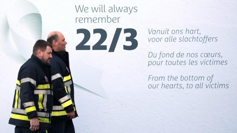 Des pompiers devant un message de commémoration dans le terminal des départs de l'aéroport de Bruxelles, avant le début de la cérémonie de commémoration du 1er anniversaire des attentats, le 22 mars 2017. (Crédit : Emmanuel Dunand/AFP)