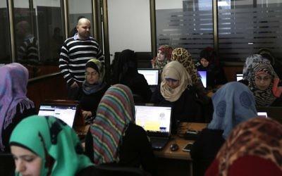 Des employées entrent des données dans les bureaux d'Unit One à Gaza (Crédit : Mahmud Hams / AFP)