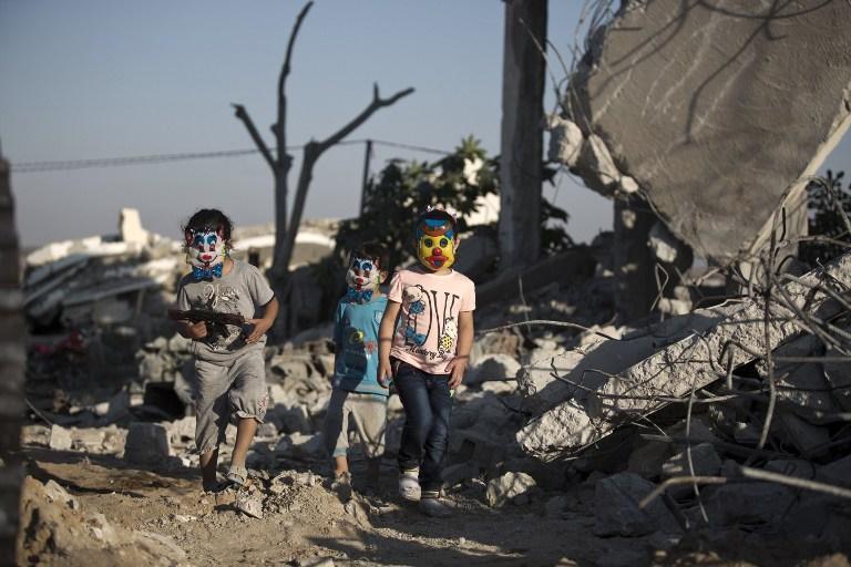 Les enfants palestiniens jouant dans les décombres de bâtiments, qui auraient été détruits pendant la guerre de 50 jours entre Israël et le Hamas pendant l'été 2014, à Gaza, le 21 juillet 2015 (Crédit : AFP / MOHAMMED ABED)