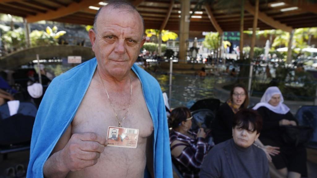 Après un bain dans les sources chaudes de Hamat Gader, Jawdat Salame montre la carte d'identité militaire de son fils Rujayah, tué par un sniper palestinien près de Rafah, dans la bande de Gaza, en 2001, son épouse Nadra est à ses côtés, le 20 février 2017. (Crédit : autorisation)
