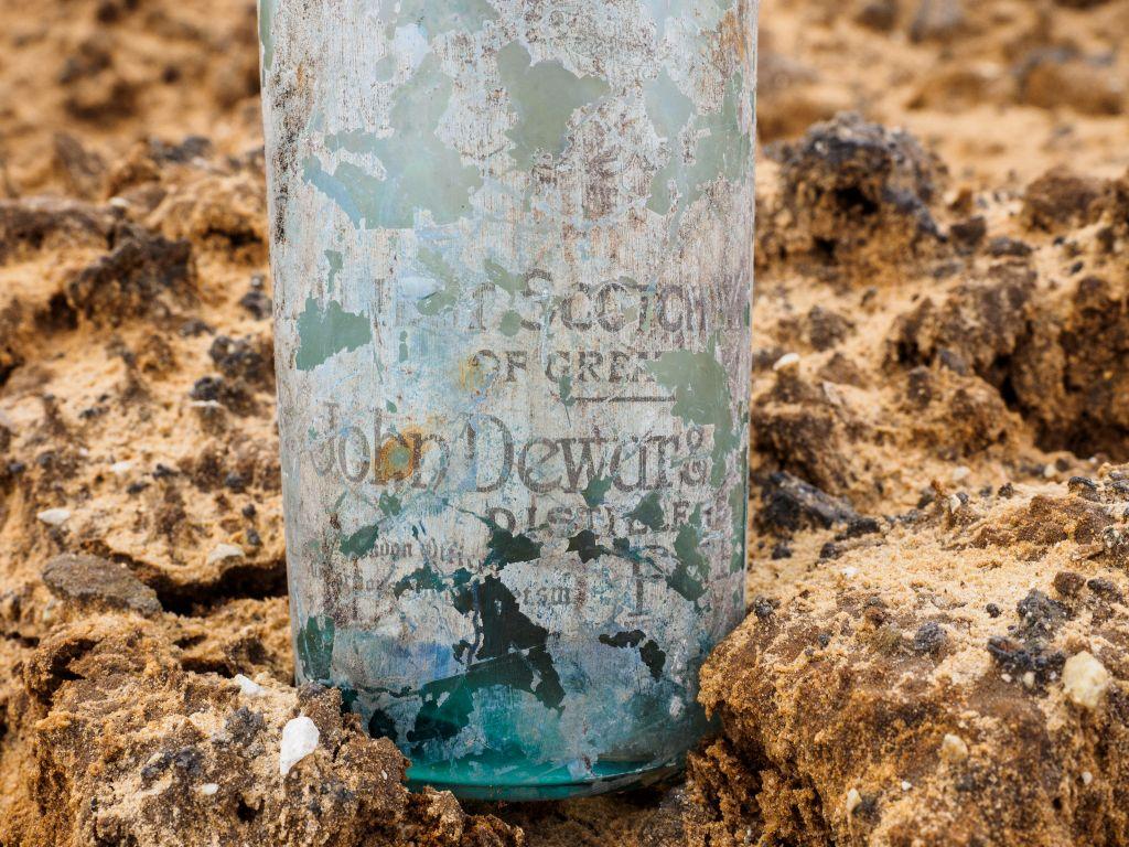 Une bouteille de whisky Dewar avec son étiquette, trouvée près de Ramle, sur une base militaire britannique de la Première Guerre mondiale, en mars 2017. (Crédit : Assaf Peretz/Autorité israélienne des Antiquités)