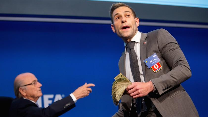 Le comédien Simon Brodkin se prépare à attaquer le président de la FIFA Joseph S. Blatter (droite) avec des faux billets durant une conférence de presse aux quartiers-généraux de la FIFA, à Zurich le 20 juillet 2015, à Zurich, en Suisse. (Crédit : JTA/Philipp Schmidli/Getty Images)