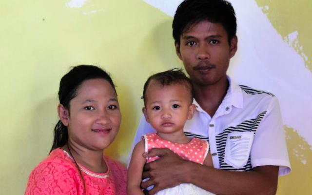 Salsa Djafar avec ses parents, Arjun Djafar (droite) et Rosna Djafar (gauche), avant de procéder à l'excision du bébé à Garantalo, en Indonésie, le 20 février 2017. (Crédit : AFP / BAY ISMOYO)