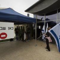 """Des employés du ministère des Affaires étrangères manifestant à Jérusalem le 24 mars 2014. Le panneau dit : """"En grève ici"""" (Crédit : Yonatan Sindel / Flash90)"""