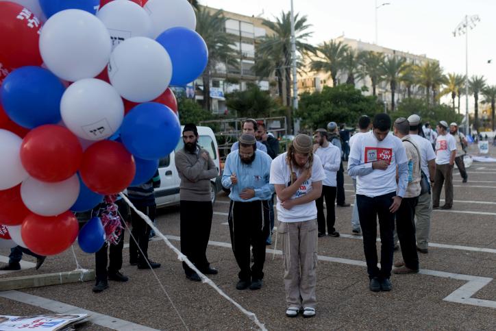 Des Israéliens prient avant un rassemblement de soutien au Premier ministre Benjamin Netanyahu, sur la place Rabin à Tel Aviv le 15 mars 2015 (Crédit : Ben Kelmer/Flash90)