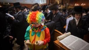 Hommes et enfants ultra-orthodoxes pendant la lecture du livre d'Esther, qui raconte l'histoire de la fête juive de Pourim, dans une yeshiva de Jérusalem, le 24 mars 2016. (Crédit : Yonatan Sindel/Flash90)