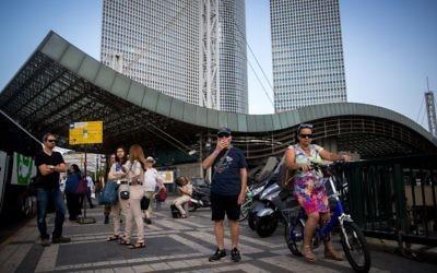 Des passagers attendent le bus près de la station Hashalom, au niveau des tours Azrieli, à Tel Aviv, le 22 septembre 2016. (Crédit : Miriam Alster/Flash90)