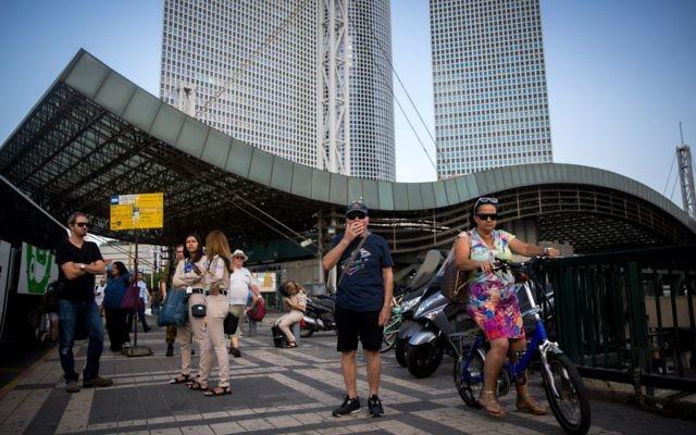Des passagers attendent le bus à la gare Hashalom, au niveau des tours Azrieli, à Tel Aviv, le 22 septembre 2016. (Crédit : Miriam Alster/Flash90)