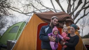 Tova et Neria Antman avec leurs filles posent pour une photo devant les tentes dans le cadre d'un mouvement de protestation contre l'évacuation d'Amona, devant le parlement israélien, le 9 février 2017 (Crédit : Hadas Parush/Flash90)