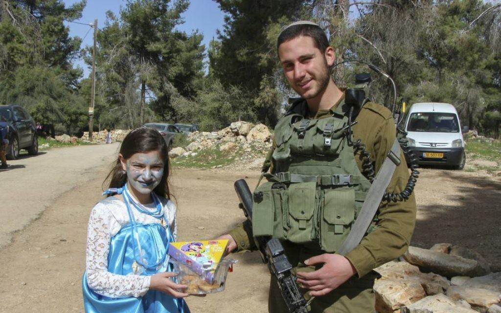 Un soldat israélien reçoit un cadeau d'une fillette à Shmurat Oz Vegaon, dans le Gush Etzion, pour la fête de Pourim, le 12 mars 2017. (Crédit : Gershon Elinson/Flash90)