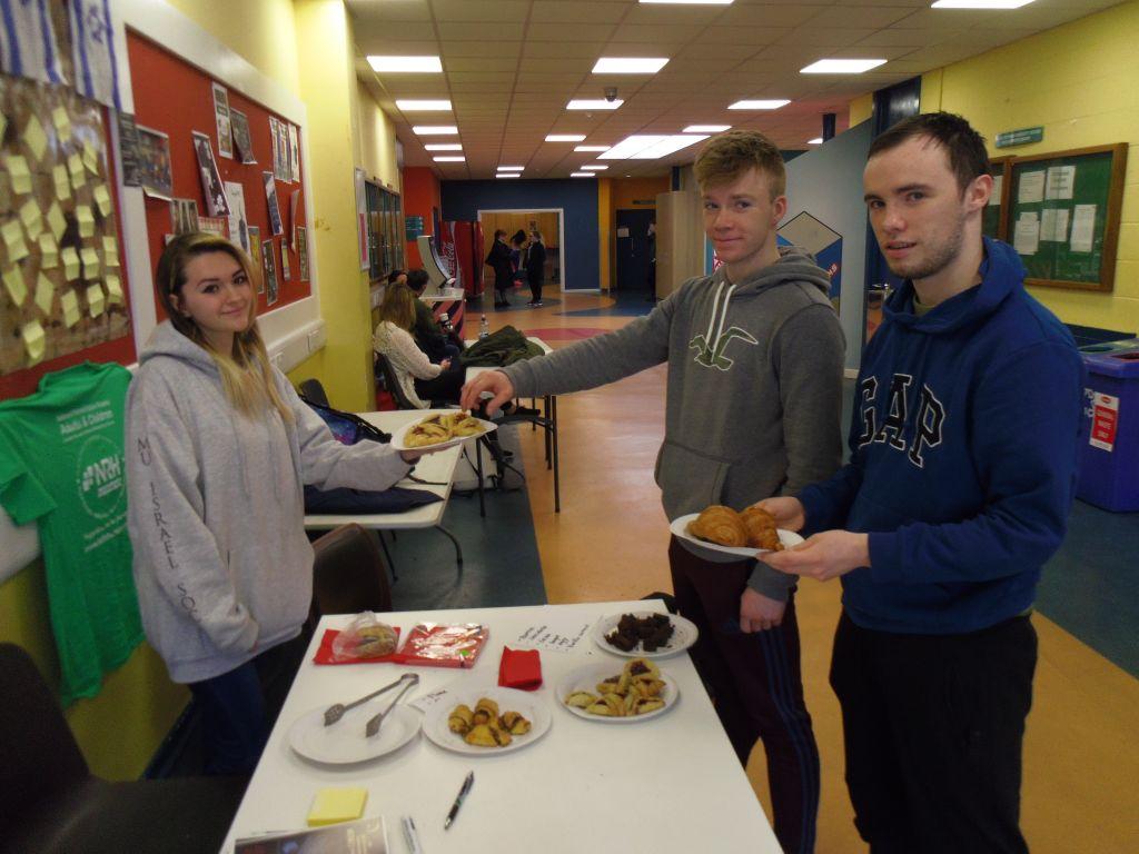 Les étudiants Rory Brosnan et Shane O'Brien goûtent des pâtisseries grâce à Louiza Vasiliu. (Crédit : Michael Riordan/Times of Israel)