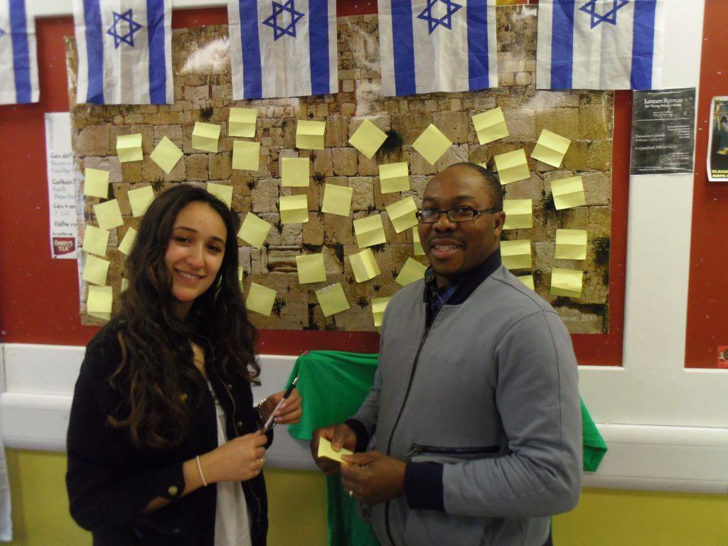 La trésorière de l'association Sara Epstein avec Goodwin Nugbasoro postant un message sur le mini mur occidental (Crédit : Michael Riordan/Times of Israel)