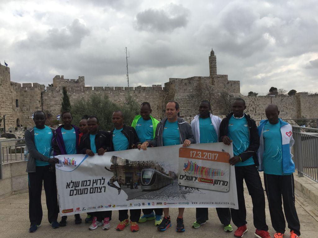 Le maire de Jérusalem Nir Barkat avec des coureurs africains de premier plan venus faire le marathon de Jérusalem avant un échauffement à la porte de Jaffa, avant l'épreuve du 17 mars 2017 (Crédit : Jessica Steinberg/Times of Israel)