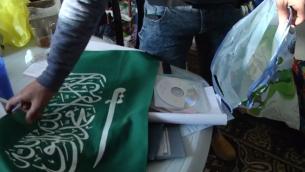 Un drapeau du Hamas et d'autres preuves collectées par la police au domicile d'un terroriste de Jérusalem Est, à Jabel Mukaber, qui a poignardé deux garde-frontières, le 13 mars 2017. (Crédit : capture d'écran Police israélienne)