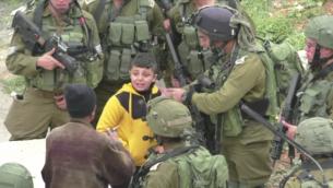Un petit garçon palestinien emmené à travers les rues de Hébron. L'armée a expliqué qu'il était soupçonné d'avoir lancé un cocktail molotov sur une implantation juive le 21 mars 2017 (Capture d'écran : B'Tselem)