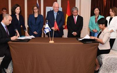 Le président Reuven Rivlin (centre) supervise la signature d'un accord de collaboration en matière d'éducation, au Vietnam. (Crédit : Koby Gideon /GPO)