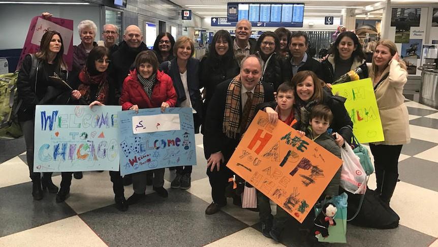 Les membres d'Am Shalom accueillent une famille de réfugiés syriens à l'aéroport international O'Hare de Chicago le 27 janvier 2017 (Autorisation : Am Shalom)