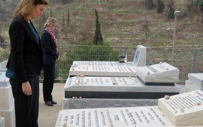 La secrétaire d'Etat chargée de l'aide aux victimes, Juliette Méadel, à gauche, devant la tombe de François-Michel Saada, assassiné à l'Hyper Casher, et l'ambassadrice Hélène Le Gal au cimetière de Givat Shaul, en mars 2017. (Crédit: Elodie Sauvage/Ambassade de France en Israël)