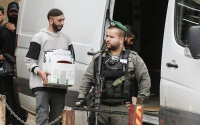 Les forces de l'ordre israéliennes dans le village d'al-Ram en Cisjordanie, durant la fermeture des bureaux aui auraient été utilisés par l'AP pour suivre les transactions immobilières entre Palestiniens et juifs, le 14 mars 2017. (Crédit : AFP PHOTO/Ahmad Gharabli)