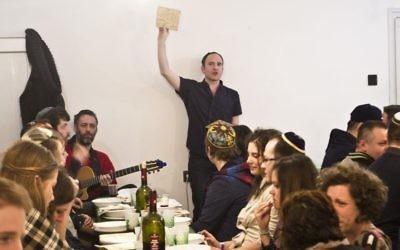 Adam Schonberger, debout, avec les autres participants lors du dîner de  seder au centre communautaire juif d'Aurora de Budapest, le 22 avril 2016 (Autorisation : Marom via JTA)