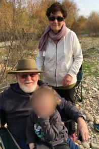 Sam et Mira Weisel avec l'un de leurs petits-enfants dans leur maison du kibboutz Nirim. Photographie non datée. (Crédit : autorisation)