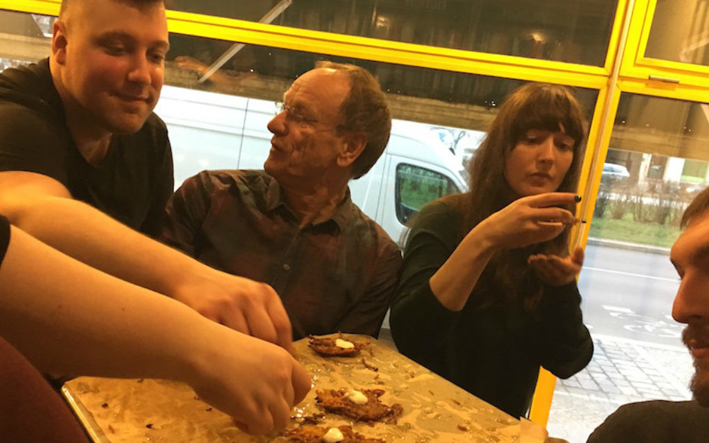 """Les participants à un événement le 20 mars célébrant la cuisine juive polonaise - dans le cadre de la """"toute première semaine de la gastronomie juive"""" de Berlin - dégustent des latkès de pommes de terre fraîchement préparés. (Toby Axelrod/via JTA)"""
