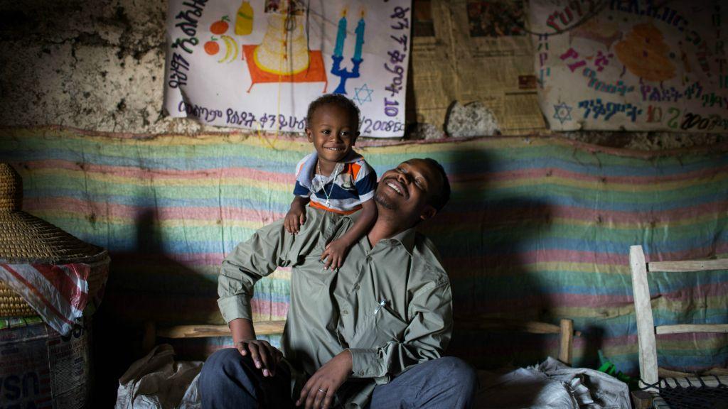 Gashaw Abinet, 29 ans avec son fils de deux ans et demi , Alieazar, dans leur habitation de Gondar, à seulement quelques pas de la synagogue HaTikva où il est chantre, le 26 avril 2016 (Crédit : Miriam Alster/Flash90)