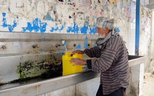 Un homme âgé remplit un bidon d'eau à un robinet à l'usine de traitement des eaux usées de l'autorité de l'Eau à Khan Yunis (Crédit : CC-BY-4.0 Muhammad Sabah B'Tselem / Wikipedia)
