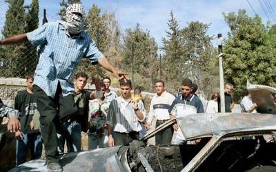 Un Palestinien célébrant sur le toit d'une voiture brûlée le lynchage de deux soldats israéliens à Ramallah, le 12 octobre 2000. (Crédit : Flash90)