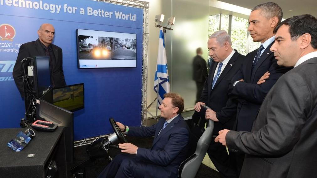 Ziv Aviram, président et directeur général de  Mobileye, fait une démonstration de voiture sans chauffeur au Premier ministre israélien  Benjamin Netanyahu, deuxième à droite, et à l'ancien président américain Barack Obama, au centre, durant une exhibition d'innovation technologique au Musée d'Israël de Jérusalem tandis qu' Amnon Shashua, à droite, co-fondateur de Mobileye et directeur de la technologie, le regarde, le 21 mars 2013  (Crédit : Kobi Gideon / GPO /FLASH90)