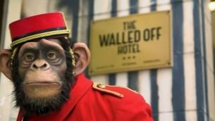 La sculpture d'un singe en uniforme de groom, devant le nouvel hôtel Walled Off, décoré par l'artiste de rue Bansky, à Bethléem en Cisjordanie. (Crédit : Capture d'écran YouTube)