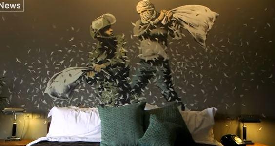 Bansky représente une bataille de polochons entre un soldat israélien et un Palestinien, peint sur le mur d'une des chambres du Walled Off Hotel, à Bethléem en Cisjordanie. (Crédit : capture d'écran YouTube)