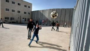 Des écoliers palestiniens jouent autour de la barrière de sécurité en Cisjordanie. Illustration. (Crédit : Flash90)