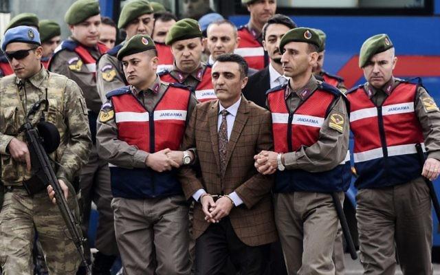 Des personnes, principalement des soldats turcs, accusées d'avoir tenté d'assassiner le président Erdogan pendant une tentative de coup d'état en juillet, sont escortées par les forces de sécurité pour être présentées au tribunal de Mugla, le 20 février 2017. (Crédit : Bulent Kilic/AFP)