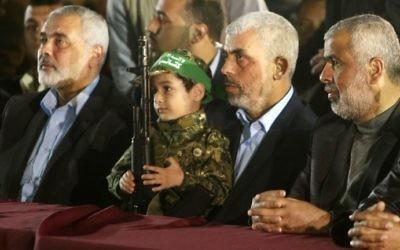 Yahya Sinwar, 2e à droite, nouveau chef du Hamas à Gaza, et Ismail Haniyeh, à gauche, près du fils de Mazen Foqaha, cadre terroriste du groupe, pendant ses funérailles, à Gaza Ville, le 27 mars 2017. (Crédit : Mahmud Hams/AFP)