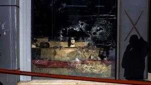 La vitrine brisée du siège du parti néo-nazi Aube dorée, à Athènes, le 31 mars 2017. (Crédit : Angelos Tzortzinis/AFP)