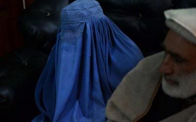 Cette photographie prise le 16 janvier 2017 montre une jeune femme afghane Nadia, 22 ans, qui tente de divorcer de son mari, lors d'un entretien, en présence de son père, avec un journaliste de l'AFP au bureau de son avocat à Jalalabad, Afghanistan (Crédit: AFP PHOTO / NOORULLAH SHIRZADA)