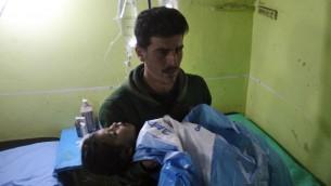Un enfant syrien inconscient transporté à l'hôpital de Khan Sheikhun, une ville tenue par les rebelles de la province d'Idleb, après une attaque au gaz toxique, le 4 avril 2017. (Crédit : Omar Haj Kadour/AFP)