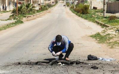 Un Syrien collecte des échantillons sur le site d'une attaque au gaz toxique à Khan Cheikhoun, dans la province syrienne d'Idleb, le 5 avril 2017. (Crédit : Omar Haj Kadour/AFP)