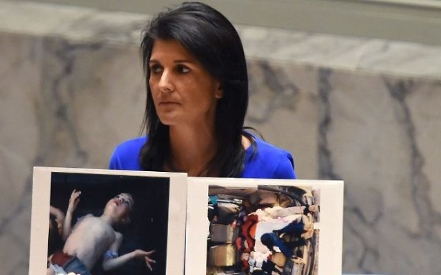 Nikki Haley, l'ambassadrice américaine aux Nations Unies, montre des photos des victimes de l'attaque meurtrière chimique présumée qui a tué des civils, et notamment des enfants, en Syrie, lors d'une réunion d'urgence du Conseil de sécurité, le 5 avril 2017. (Crédit : Timothy A. Clary/AFP)