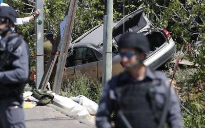 Les forces de sécurité israéliennes sur le site d'une attaque à la voiture bélier, près de l'implantation d'Ofra, en Cisjordanie, le 6 avril 2017. (Crédit : Thomas Coex/AFP)