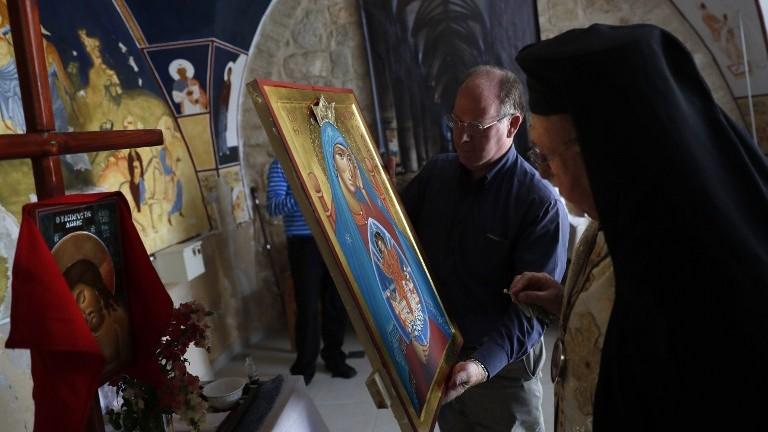 L'archevêque Joseph Jules Zerey; à droite, bénit les étudiants étrangers du Bethlehem Icon Center pendant leur cours, dans la ville biblique de Bethléem, en Cisjordanie, le 11 avril 2017. (Crédit : Thomas Coex/AFP)