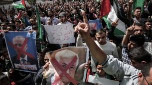 Des partisans gazaouis du Hamas pendant une manifestation contre le président de l'Autorité palestinienne Mahmmud Abbas, au centre, et son Premier ministre Rami Hamdallah à Khan Yunis, le 14 avril 2017. (Crédit : Said Khatib/AFP)