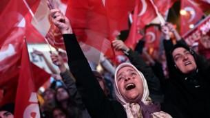 Une femme soutenant le président turc brandit le drapeau national en signe de victoire lors d'un rassemblement au siège du parti conservateur de la Justice et du Développement (AKP) le 16 avril 2017 après les résultats d'un référendum national qui déterminera la destinée future du pays (Crédit : AFP/Ozan Kose)