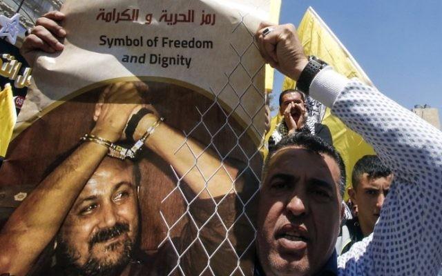 Un homme avec une photo du terroriste palestinien condamné Marwan Barghouthi pour demander sa libération pendant une manifestation de soutien aux détenus en grève de la faim à Hébron, en Cisjordanie, le 17 avril 2017. (Crédit : Hazem Bader/AFP)