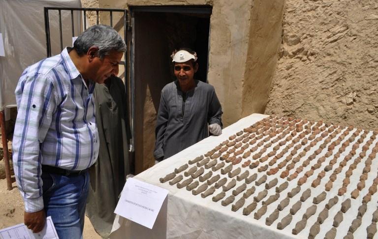 Un archéologue égyptien, à droite, devant les artefacts découverts dans une tombe de 3 500 ans dans la nécropole de Draa Abul Nagaa, proche de Louxor, en Egypte, le 18 avril 2017. (Crédit : AFP/Stringer)