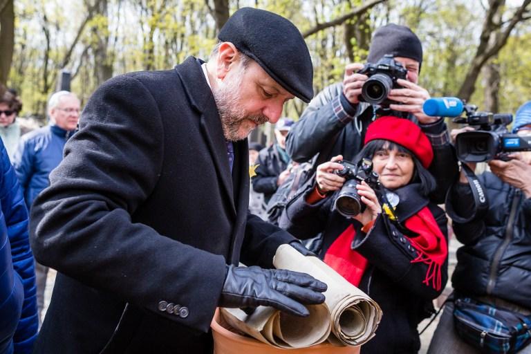 Le grand rabbin de Pologne, Michael Schudrich, prépare les rouleaux de Torah abîmés avant les funérailles au cimetière juif de Varsovie, le 19 avril 2017. (Crédit : Wojtek Radwanski/AFP)