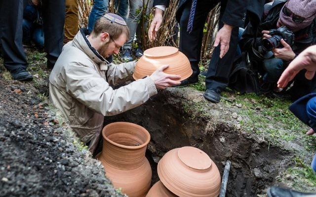 Le rabbin Moshe Bloom pendant les funérailles de rouleaux de la Torah au cimetière juif de Varsovie, le 19 avril 2017. (Crédit : Wojtek Radwanski/AFP)
